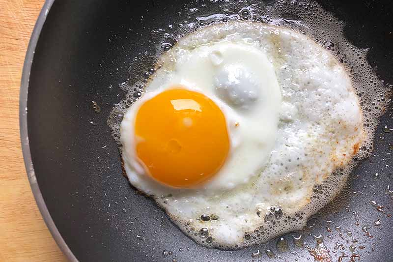 Horizontal image of frying a savory breakfast in the skillet.
