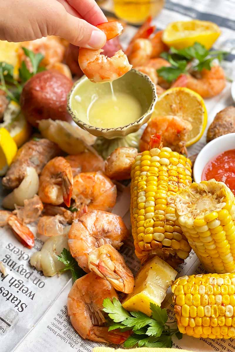 Vertical image of a hand dipping shrimp in melted butter next to scattered seafood and vegetables.