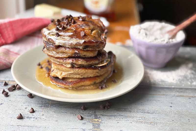 Horizontal image of a tall stack of pancakes with maple syrup and chocolate chips next to a bowl of flour and a red plaid towel.