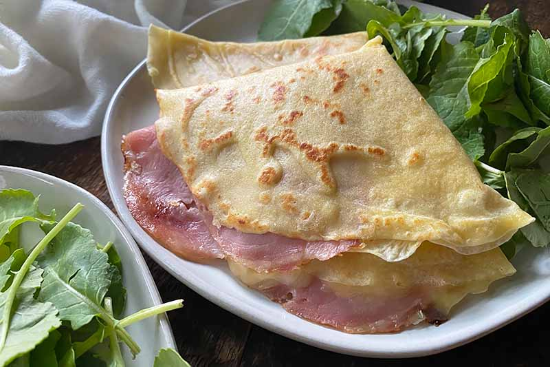 Horizontal image of two filled crepes on a plate next to salad greens.