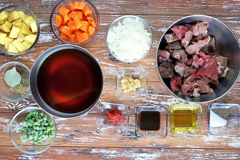 Horizontal image of bowls of assorted prepped ingredients on a wooden surface.