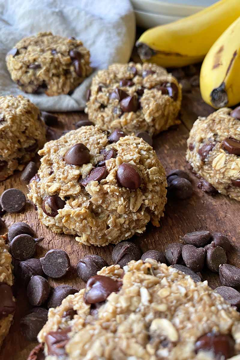 Vertical image of scattered small baked goods with oats and chocolate chips.