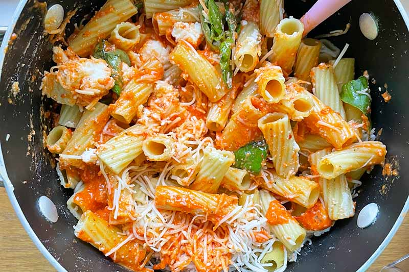 Horizontal image of mixing together cooked rigatoni with sauce, cheese, and herbs.
