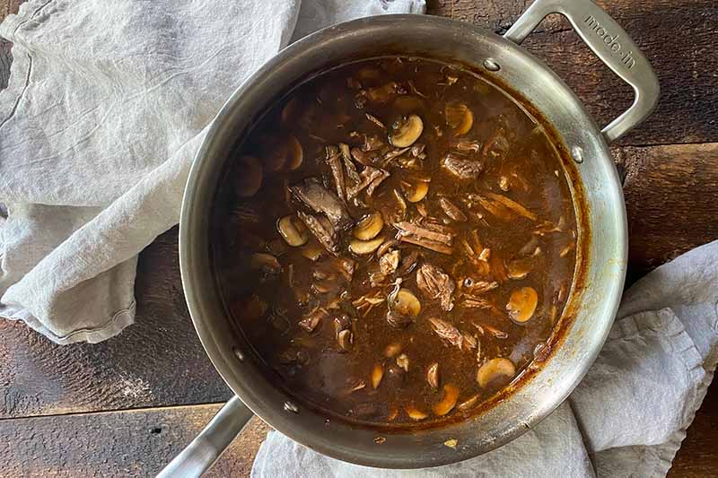 Horizontal image of a dark brown soup with meat and slices of vegetables in a pot.