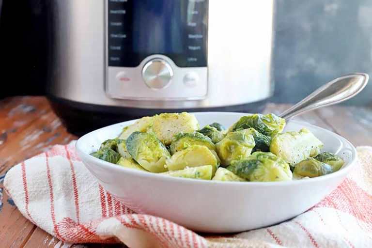 Horizontal image of a white bowl filled with seasoned green vegetables on a red checkered towel in front of a kitchen appliance.
