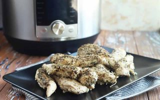 Horizontal image of seasoned white meat pieces on a black plate, with a kitchen appliance in the background.