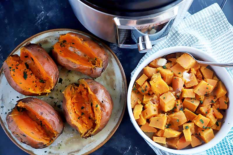 Horizontal image of a plate of four split whole orange root vegetables and a bowl of cubed orange root vegetables garnished with chopped herbs.