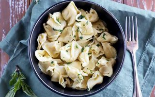 Horizontal image of a black bowl filled with stuffed pasta lightly seasoned with chopped fresh herbs on a blue napkin next to a fork.