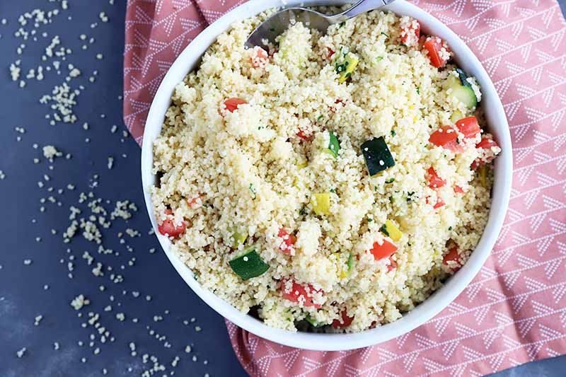 Horizontal image of a large white dish filled with grains mixed with chopped vegetables on a red towel.