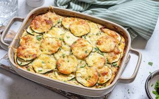Horizontal image of a casserole dish with zucchini slices and melted cheese on a blue towel