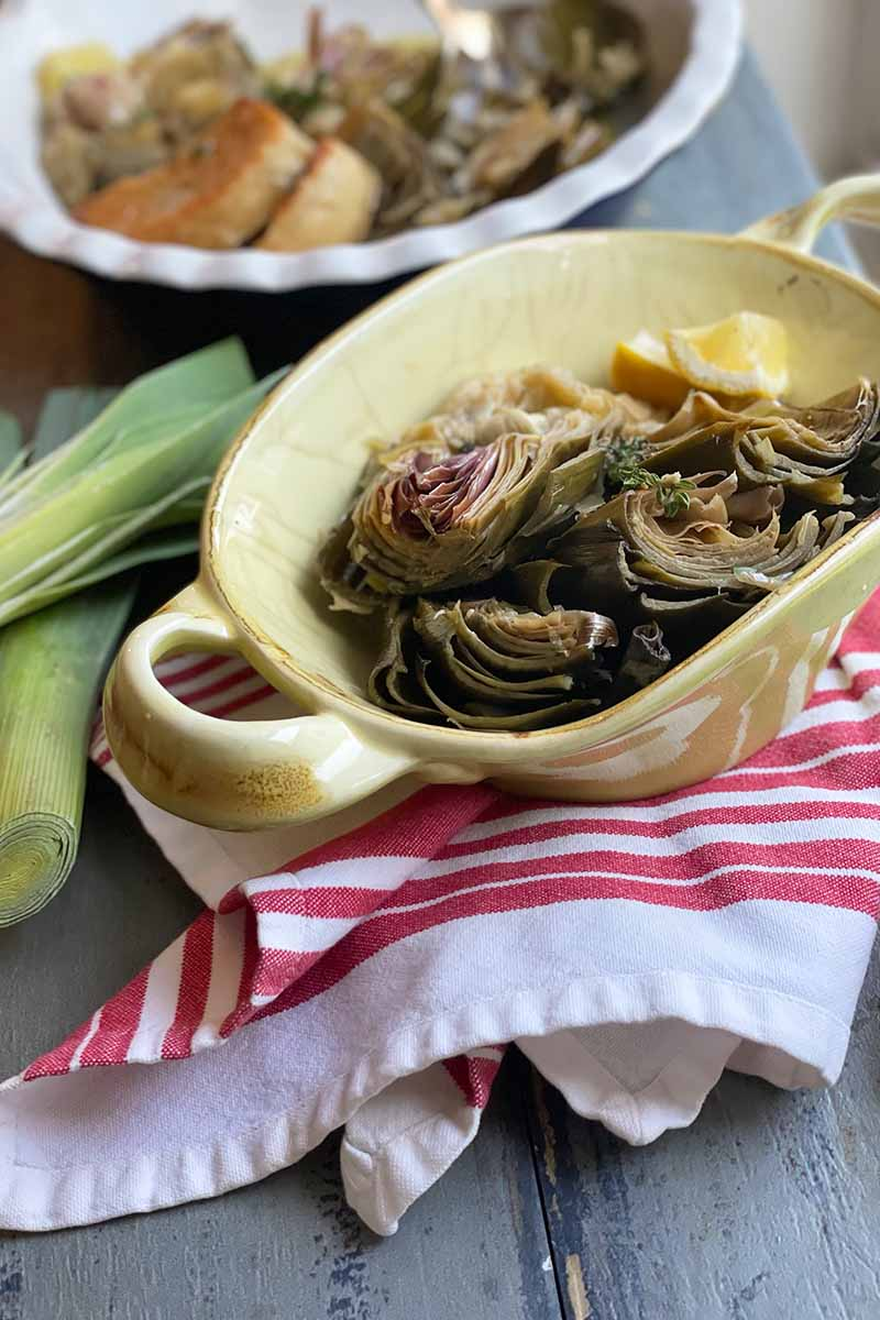 Vertical image of a green casserole dish with vegetables and lemon wedges on a red-striped towel next to leeks.