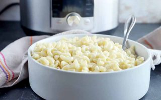 Horizontal image of a large bowl full of elbow macaroni with a spoon in front of a towel and a kitchen appliance.