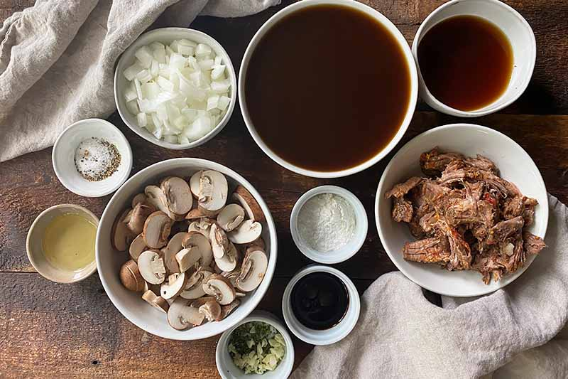 Horizontal image of assorted prepped ingredients in various white bowls.