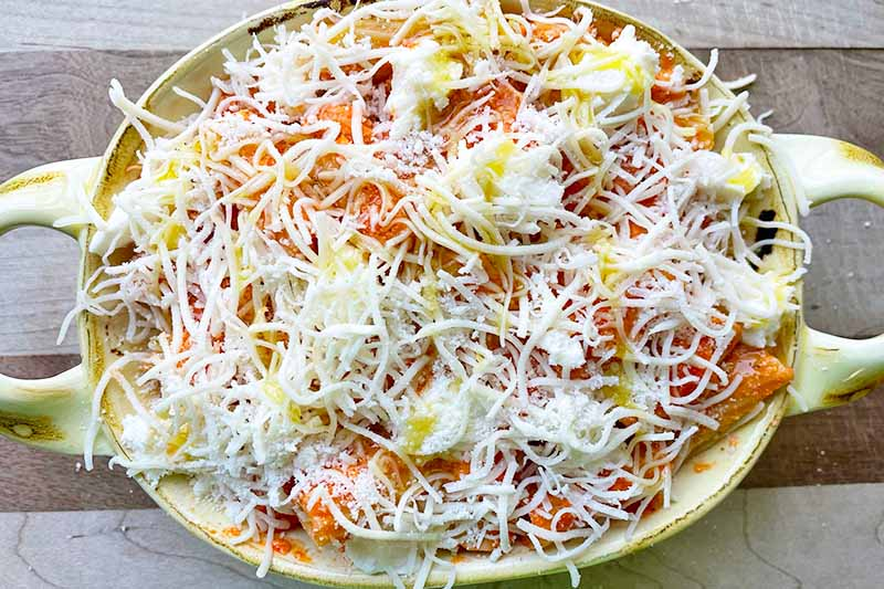 Horizontal image of a green dish filled with rigatoni, sauce, and different cheeses.