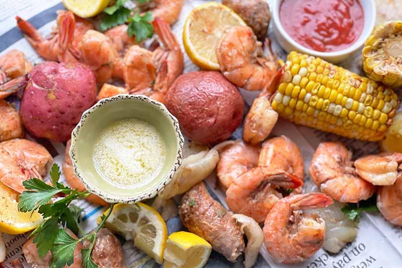 Horizontal image of shrimp, sausage, lemons, and assorted vegetables on newspaper next to dip.