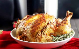 Horizontal image of an entire seasoned poultry on a white plate in front of a kitchen appliance on a red towel.