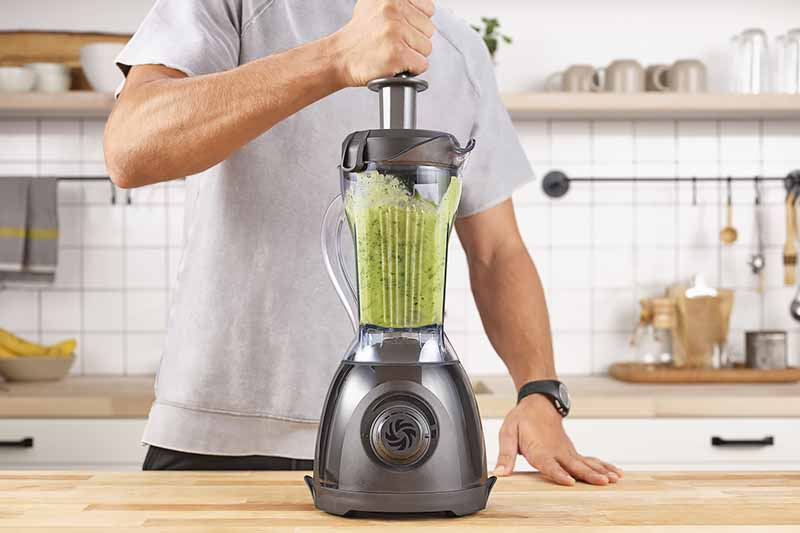 Horizontal image of a man using the tamper to make a green smoothie in the kitchen.