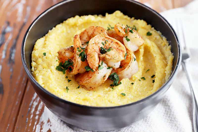 Horizontal image of a black bowl full of grits topped with seasoned shrimp, on top of a white towel.