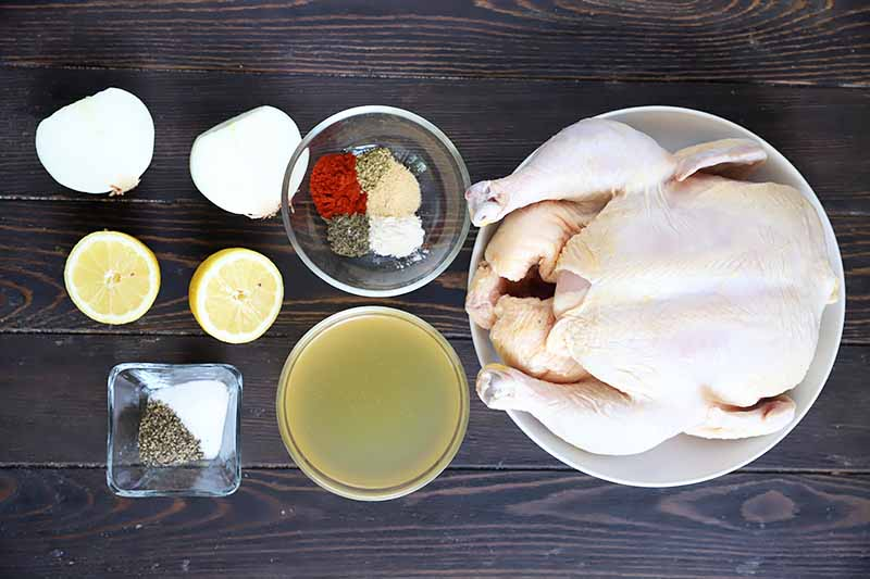 Horizontal image of an entire raw poultry next to assorted ingredients in small bowls.