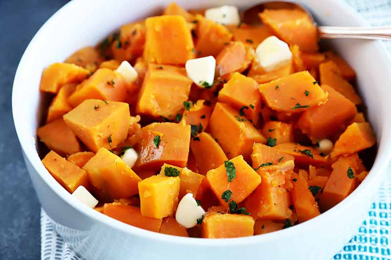 Horizontal image of a large white bowl full of cubed orange root vegetables garnished with chopped herbs and pieces of butter.