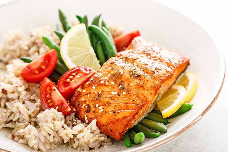 Horizontal image of salmon, vegetables, and rice in a white bowl.