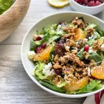Horizontal image of a white bowl with lettuce, orange segments, pomegranate seeds, and crumbles of cheese on a red striped towel.