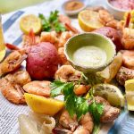 Horizontal image of shrimp, sausage, lemons, and assorted vegetables on newspaper next to dip and beer.