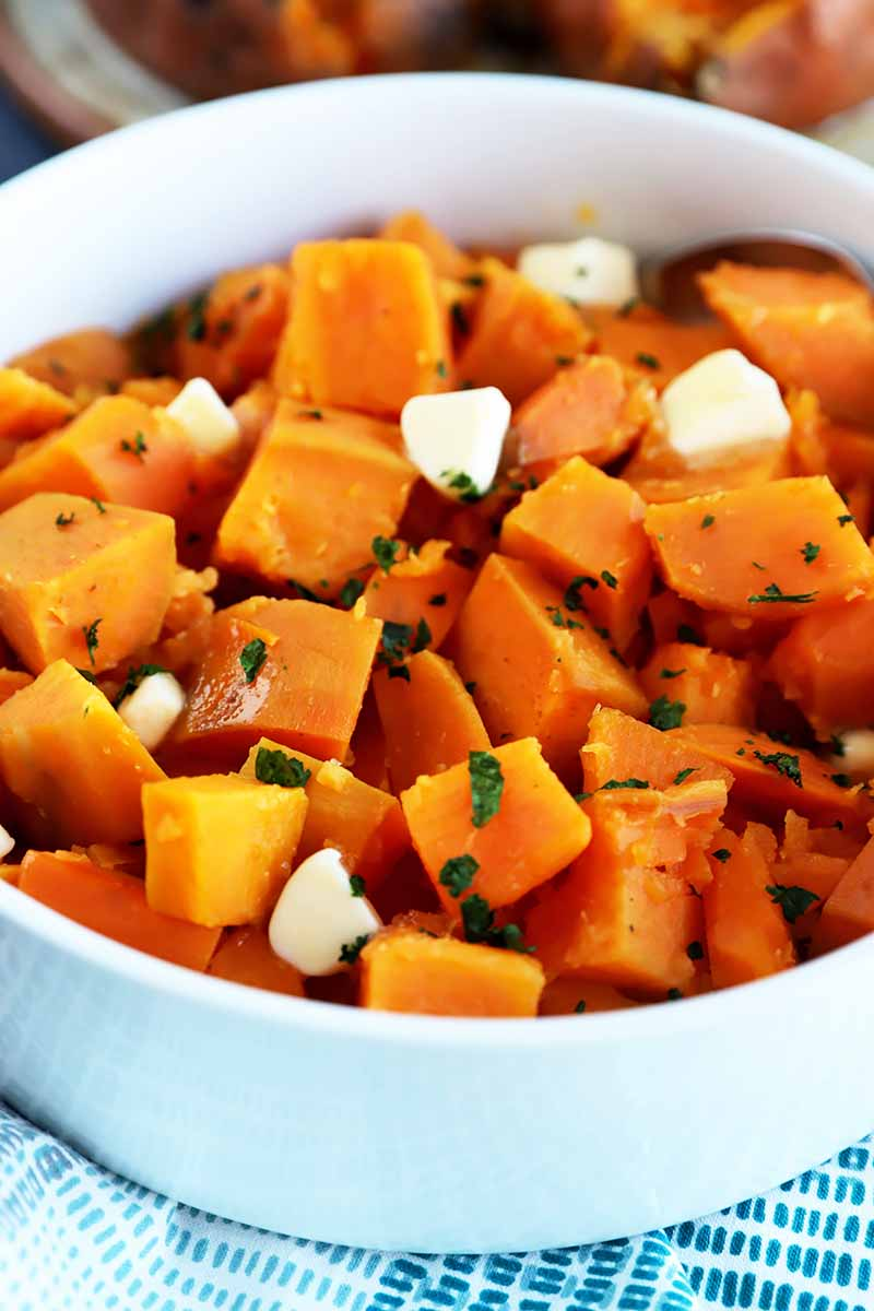 Vertical image of a large white bowl full of cubed orange root vegetables garnished with chopped herbs and pieces of butter.