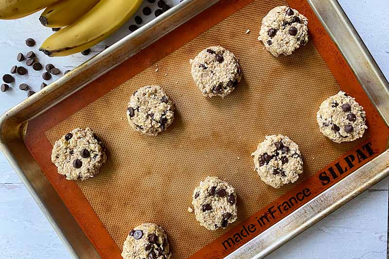Horizontal image of portioned mounds of unbaked dough on a baking sheet with a silicone baking mat.