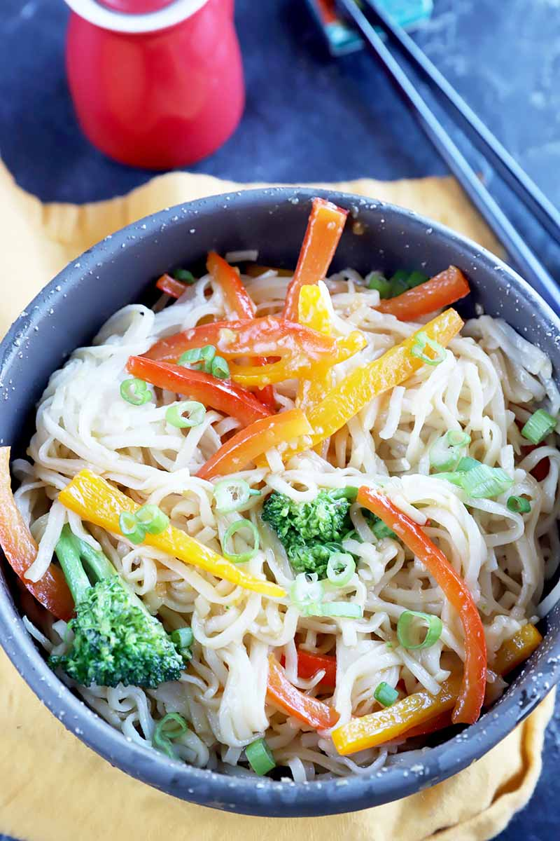 Vertical top-down image of a bowl of lo mein with peppers and broccoli next to chopsticks.