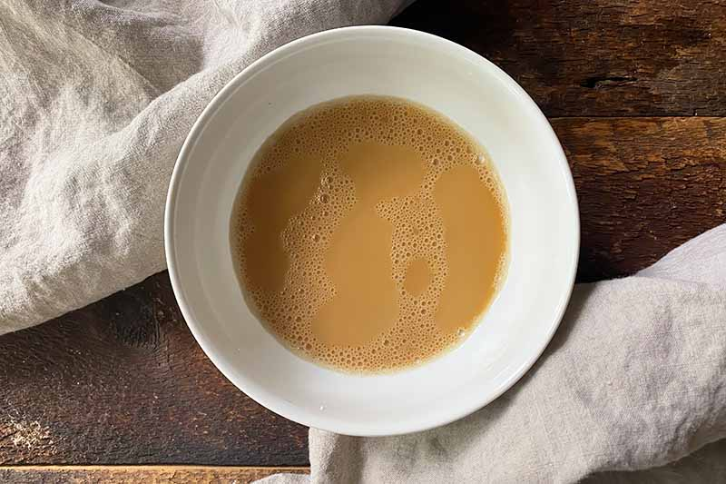 Horizontal image of a light brown slurry in a white bowl.