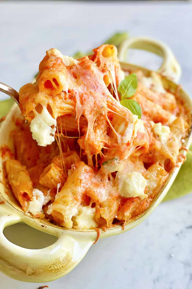 Vertical image of a rigatoni and cheese dish in a green pan.