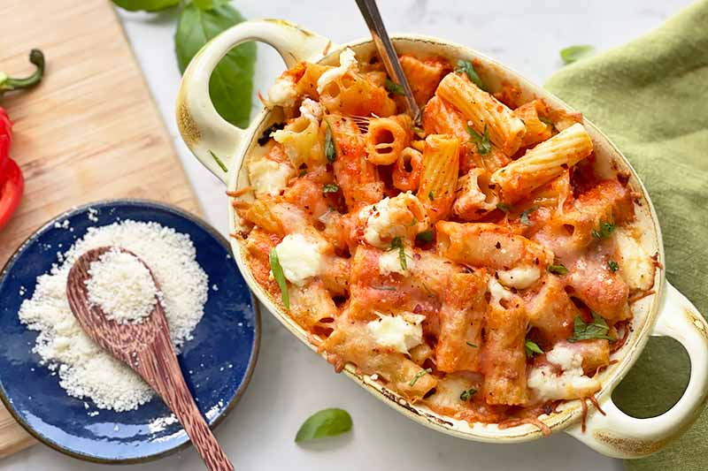 Horizontal image of a green platter with a rigatoni, cheese, and sauce mixture next to a blue bowl with grated cheese.