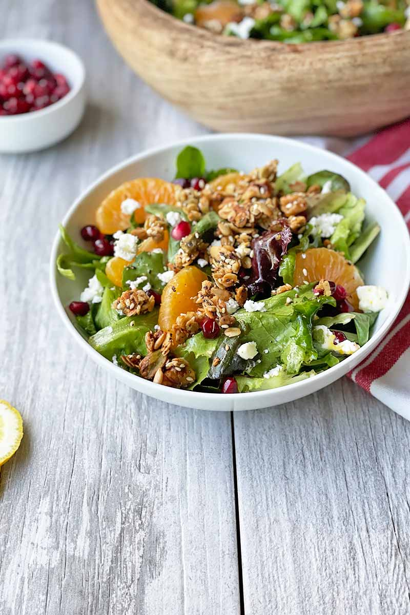Vertical image of a white bowl fill with lettuce, orange segments, pomegranate seeds, and cheese crumbles on a gray wooden surface.