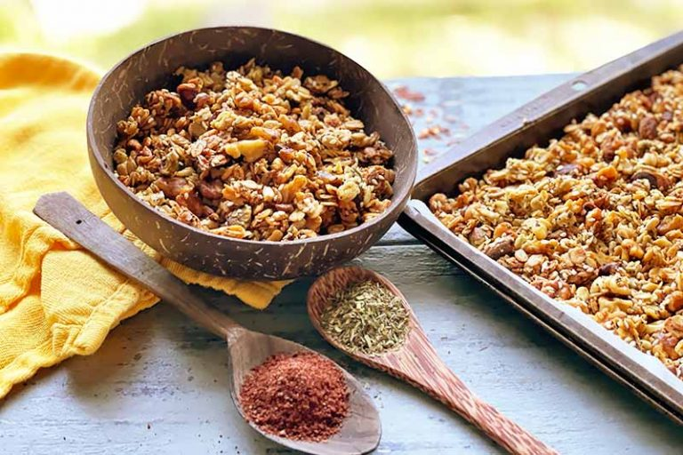 Horizontal image of a wooden bowl and a baking sheet filled with an oat, nut, and seed mixture next to a yellow towel and wooden spoons filled with spices.