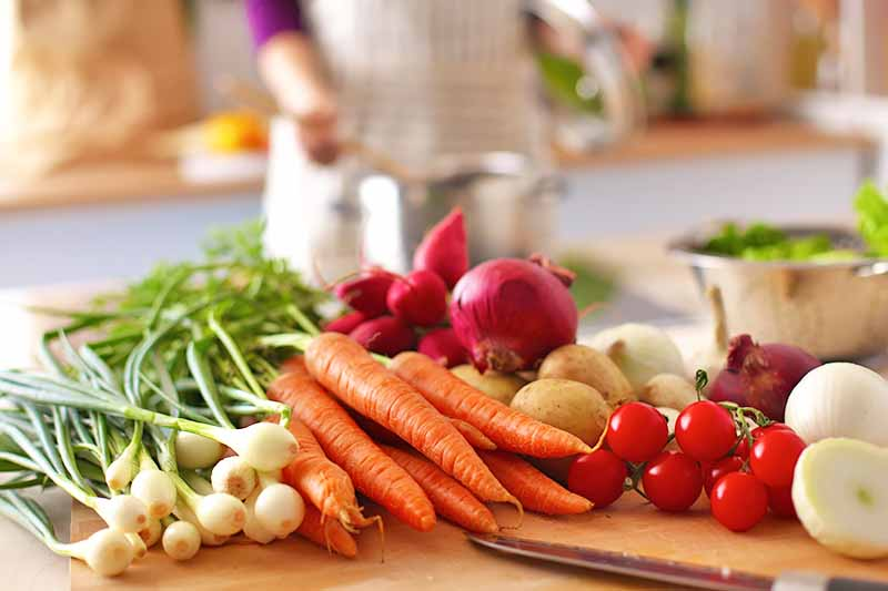 Horizontal image of assorted fresh vegetables on a countertop in the kitchen with a women cooking in the background.