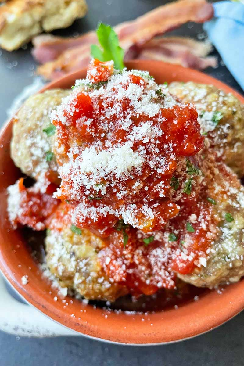 Vertical close-up image of individual mounds covered in red sauce and grated cheese with herb garnish.