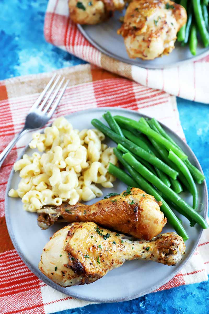 Vertical image of plates with pieces of seasoned poultry, macaroni and cheese, and greens beans on checkered red towels with forks.
