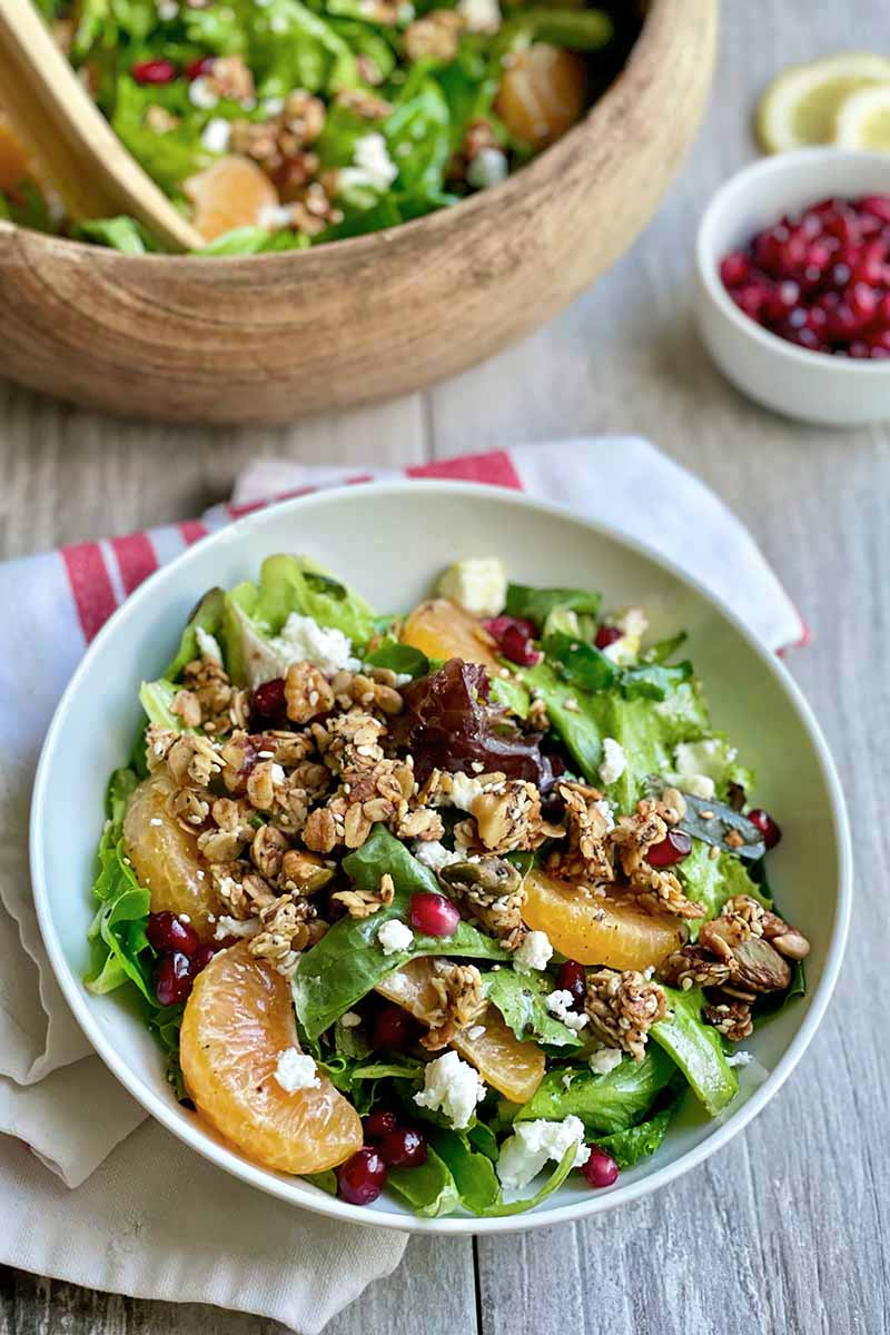 Vertical image of a white bowl filled with greens, orange segments, pomegranate seeds, and fresh cheese.