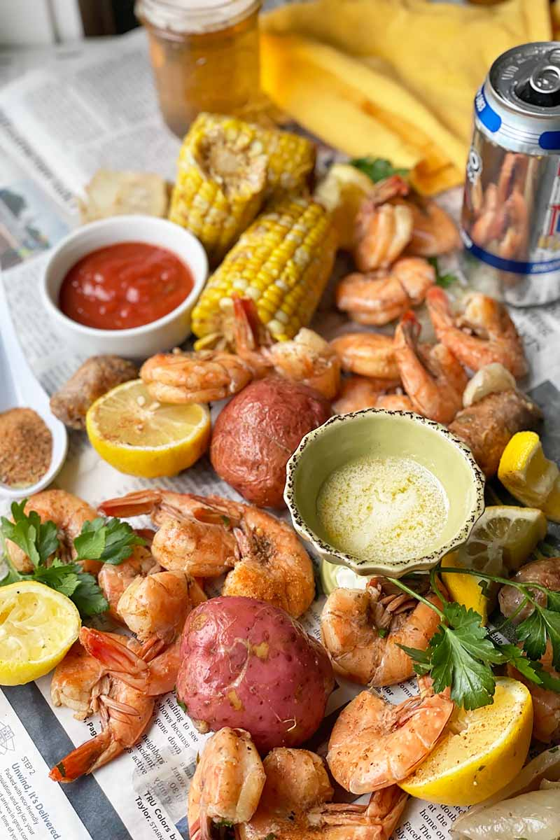 Vertical image of scattered vegetables, seafood, and lemon slices next to dips in bowls on newspaper.