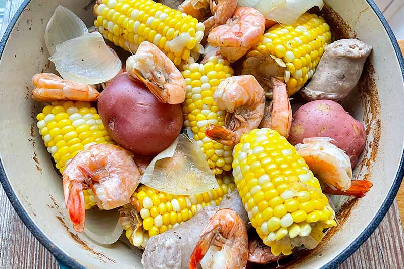Horizontal image of corn, potatoes, shrimp, and sausage in a pot.