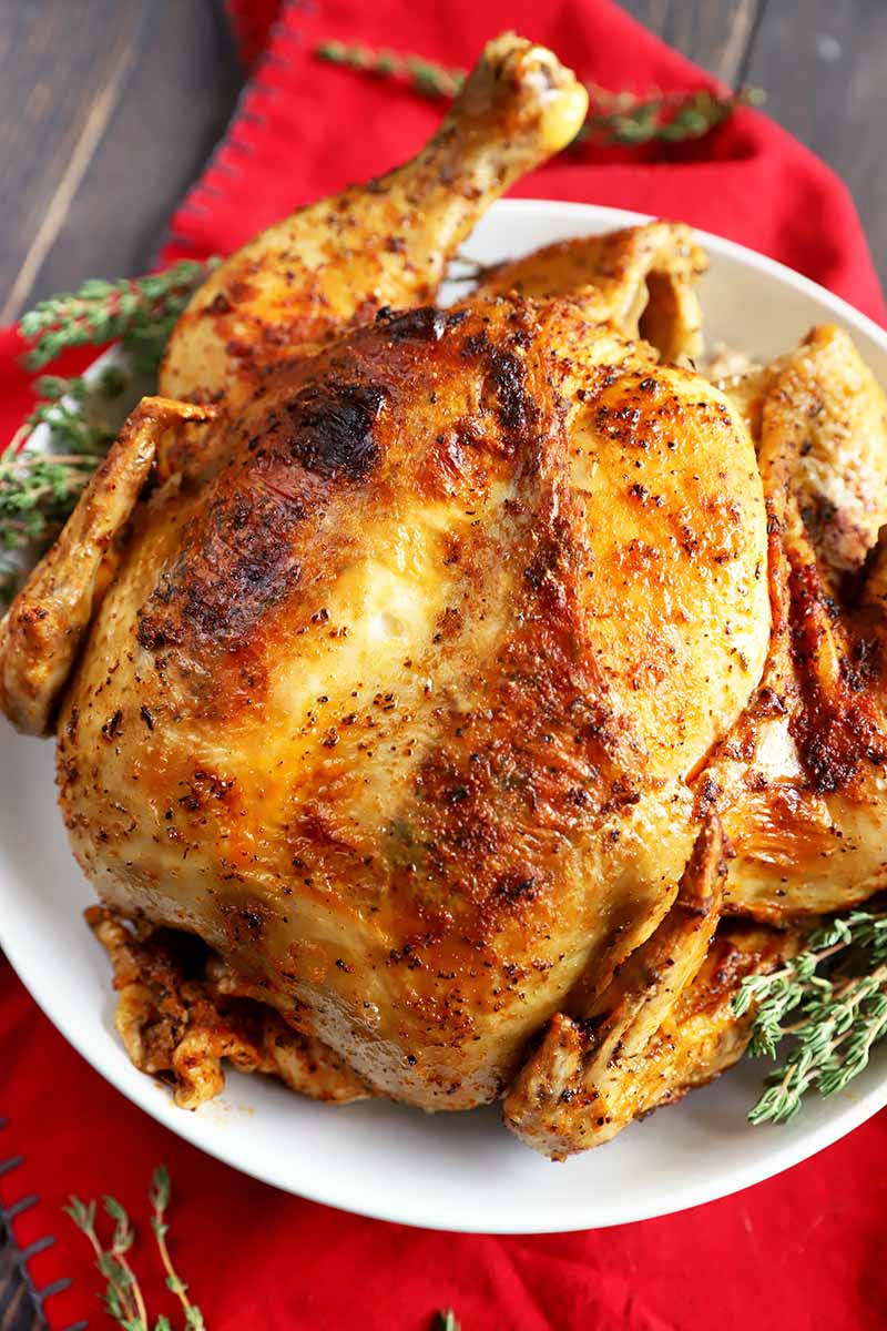 Vertical image of an entire seasoned poultry on a white plate with fresh herbs on a red towel.