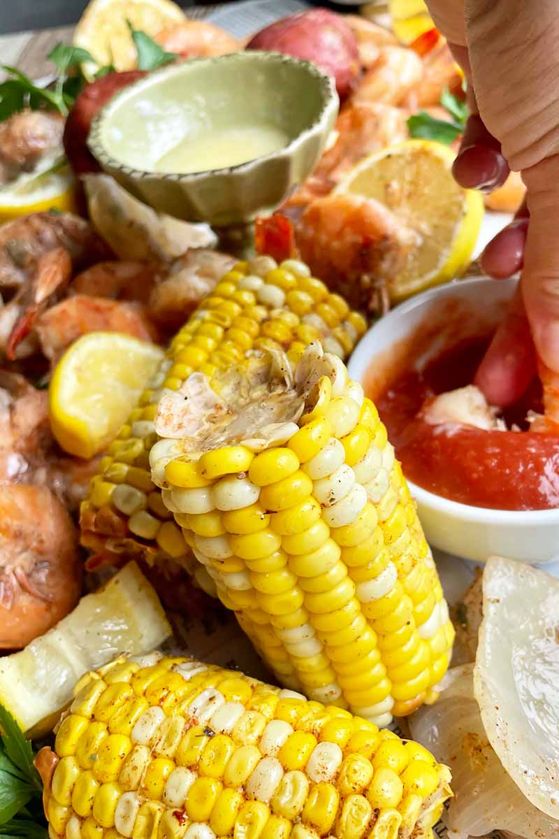 Vertical close-up image of pieces of seasoned corn on the cob in front of assorted vegetables, shrimp, and lemon slices next to bowls of dip.