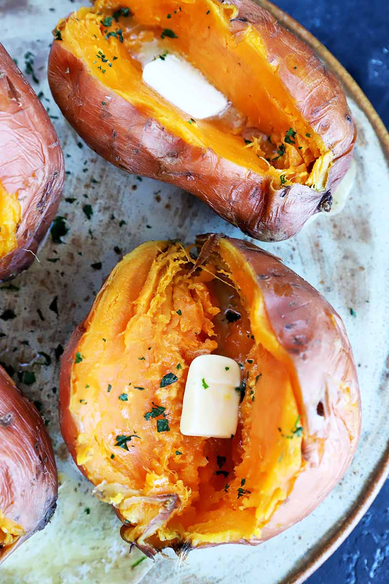 Vertical image of two split whole orange root vegetables with cubes of butter and chopped herbs.