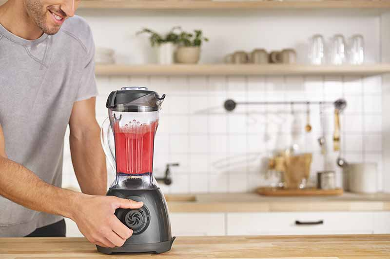 Horizontal image of a man using a blender for a pink smoothie in a kitchen.