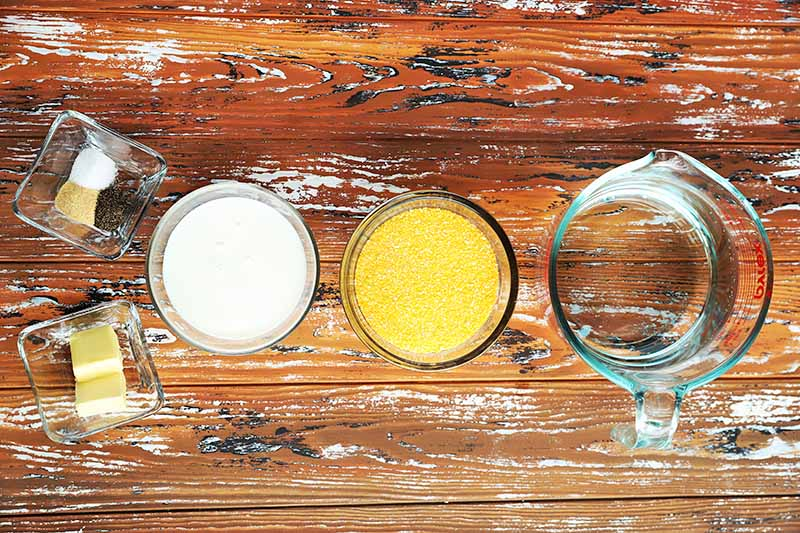 Horizontal image of seasonings, milk, cornmeal, and water in glass bowls on a wooden surface.