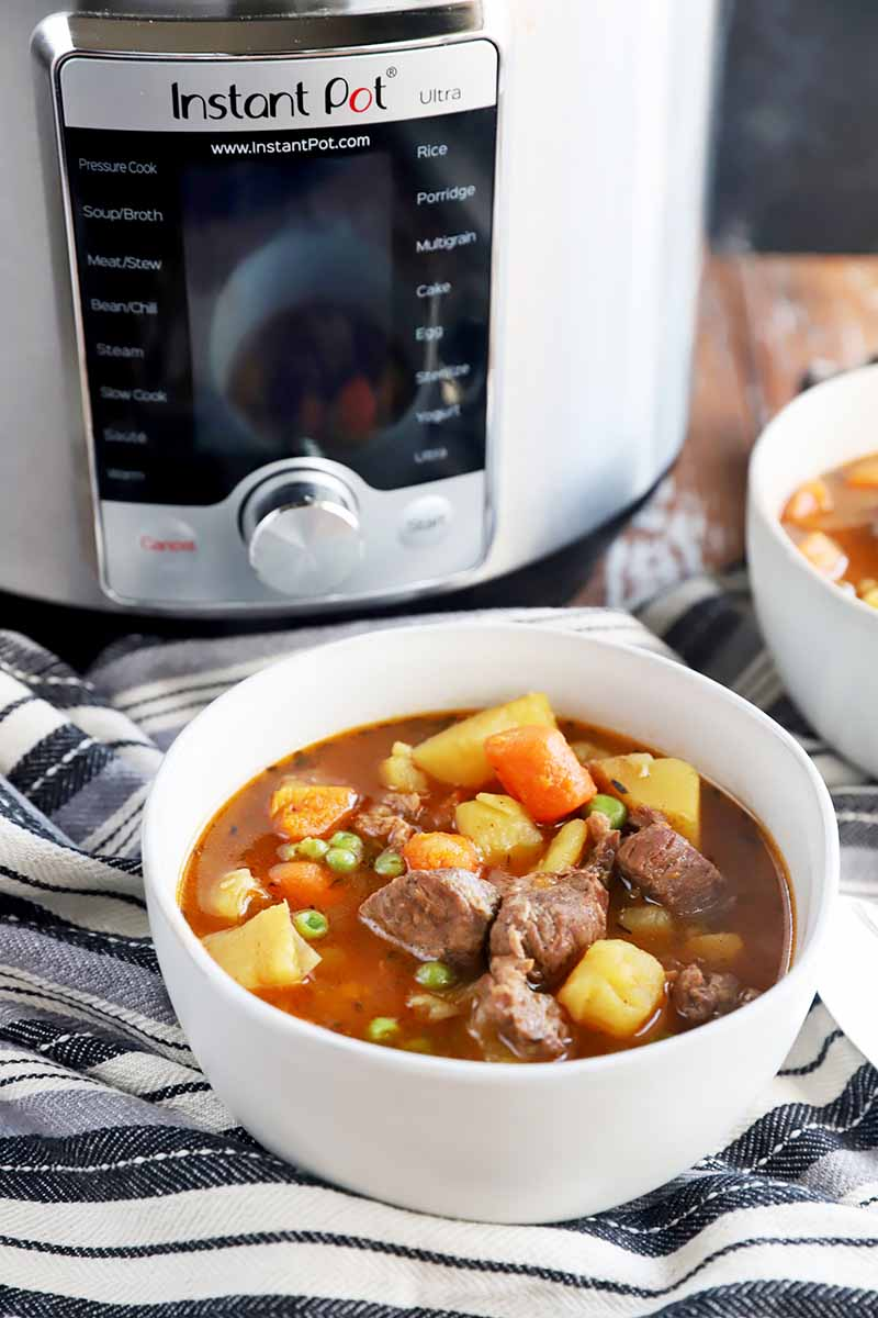 Vertical image of white bowls filled with a soup with chunks of meat and vegetables on a striped napkin, with a large kitchen appliance in the background.