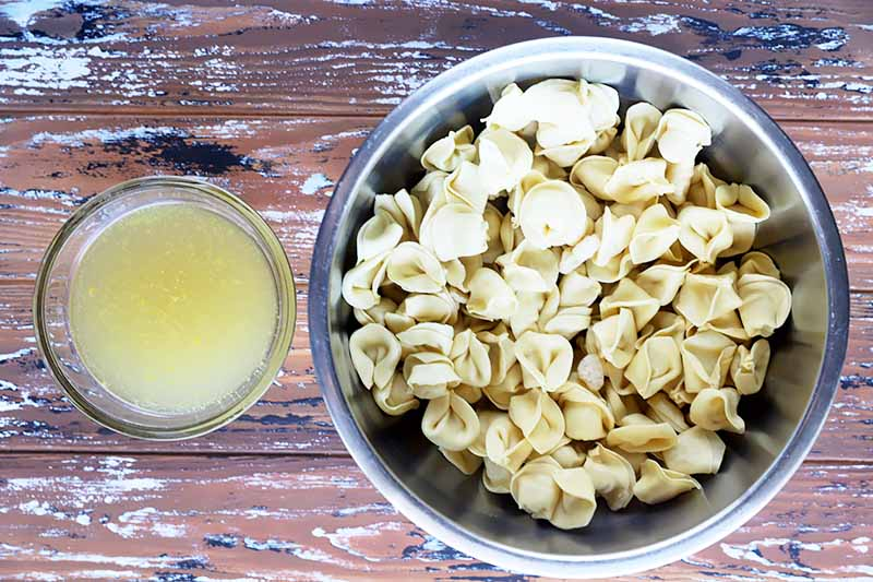 Horizontal image of a bowl of stock and a larger bowl of stuffed pasta.