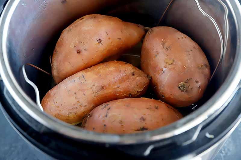Horizontal image of cooked whole unpeeled root vegetables in a pot with a wire interior rack.