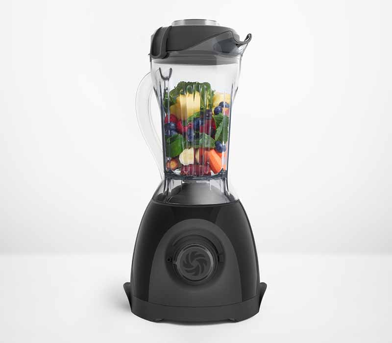 Horizontal image of a blender filled with pieces of fruit and vegetables.